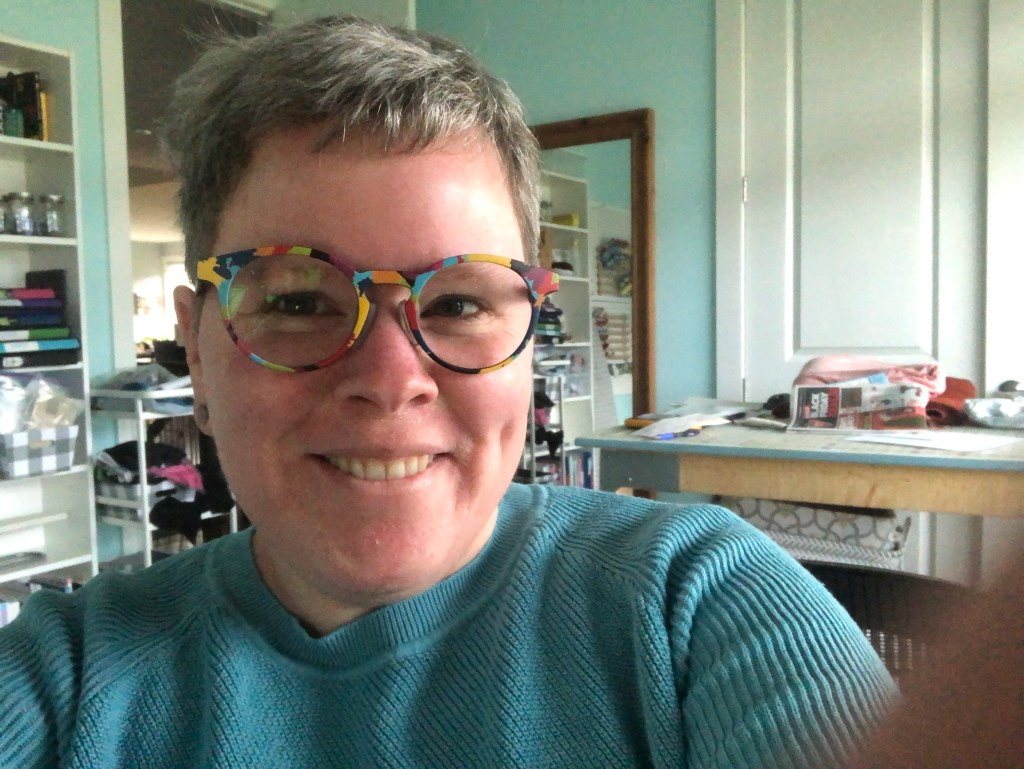 "A ""selfie"" picture of Kerry smiling at the camera.  She is wearing multi coloured glasses and a teal knit top.  The room behind her looks like a sewing room or craft space."