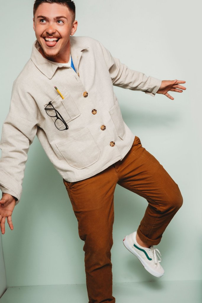 A young person models the Friday Pattern Company Ilford jacket, which is bone-colored and features tortoiseshell-esque buttons. A pair of glasses and a pencil are placed in the right breast pocket. The jacket is paired with a pair of rust-colored trousers and ivory sneakers with a green stripe along the sides. They are striking a fun pose, balanced on their right leg with their left bent at the knee and not touching the floor; they are sticking their tongue out playfully.