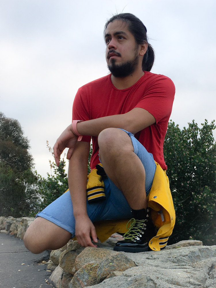The author is crouched down on a stone wall, wearing light blue denim shorts, a plain red t-shirt, and has a yellow jacket tied around his waist. He looks serenely into the distance, his arm casually leaning on his knee.