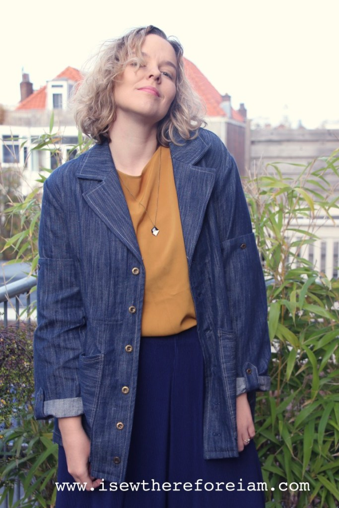 A young woman models her Closet Case Patterns Sienna Maker Jacket, which she has made in denim. She pairs it with a mustard-colored top and dark navy bottoms. She stands outside, with various plants and other houses in the background.