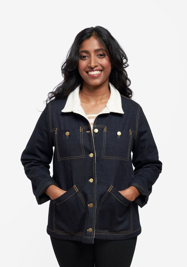 A model wears a Grainline Studio Thayer jacket made of denim. The jacket features a contrasting white collar and facing. The model wears black pants and a camel-and-white striped tee, and her long black hair cascades behind her shoulders as she smiles into the camera.