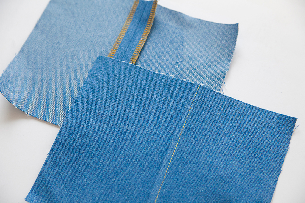 Image of fabric alternative seam finished on denim. Two fabric samples are pictured, one with a serged seam allowance, and the other finished with a flat felled seam.