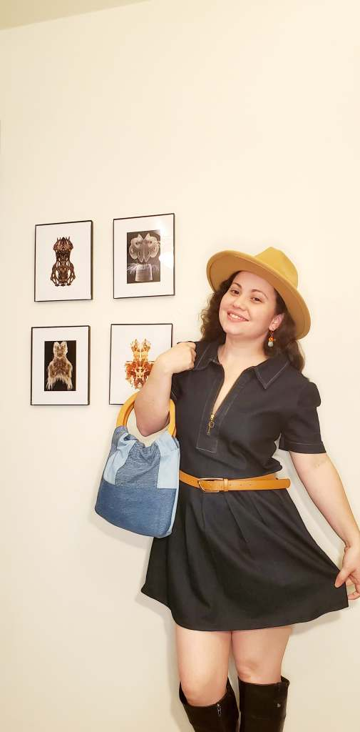 A woman in a hat and denim dress posing with a denim bag
