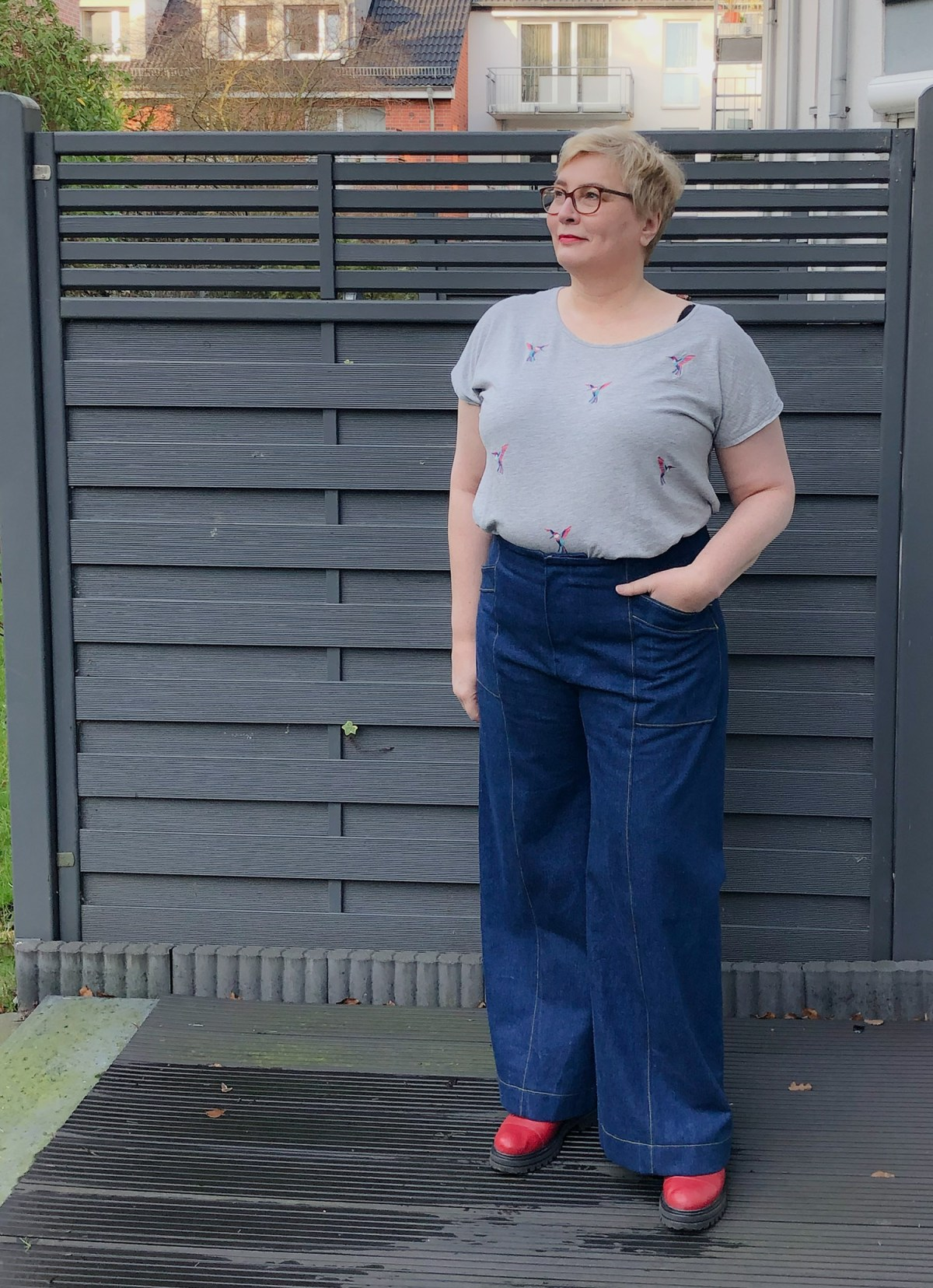 Bianka, a white woman with short blond hair and glasses, models her new wide-legged jeans.