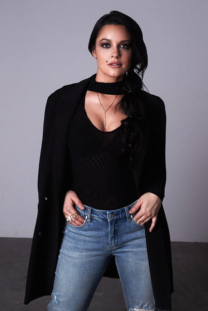 A front view of Jaclyn, looking positively vampish and overall fabulous. She wears distressed jeans, a black top with a deep scoop neckline, and a black jacket and scarf worn over her shoulders like a dramatic cape. She has smoky, almost goth makeup.