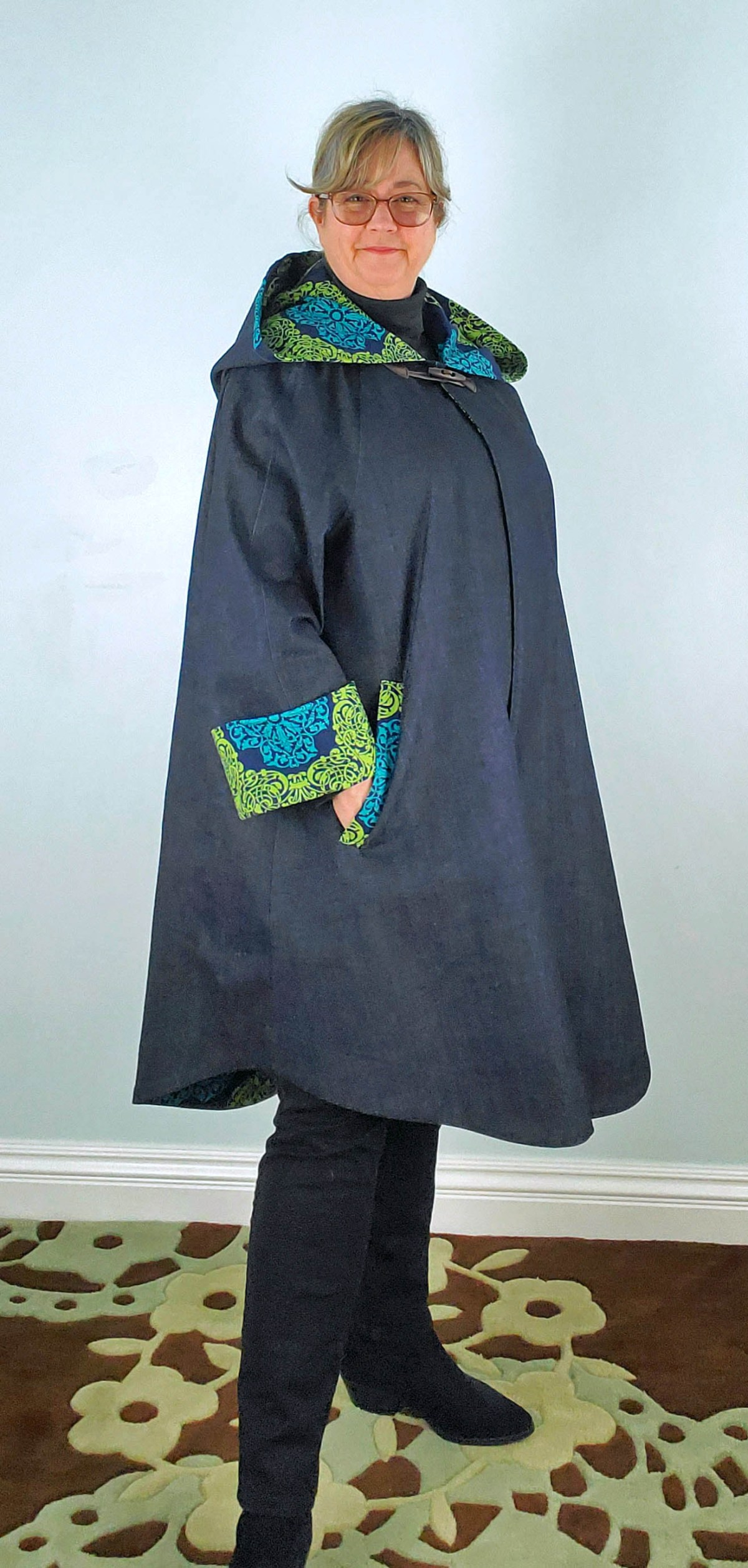 Kim models her long denim jacket. The large hood drapes over her shoulders, showing the contrasting bright green and blue patterned lining fabric. She has used the same contrast fabric for the jacket's cuffs and welt pockets; her right hand rests in the right jacket pocket.