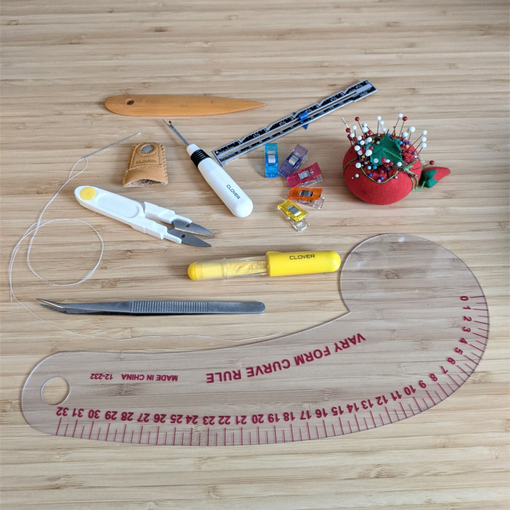 Tools for patient sewing, including a pin cushion, seam ripper, tweezers, and a pattern master.
