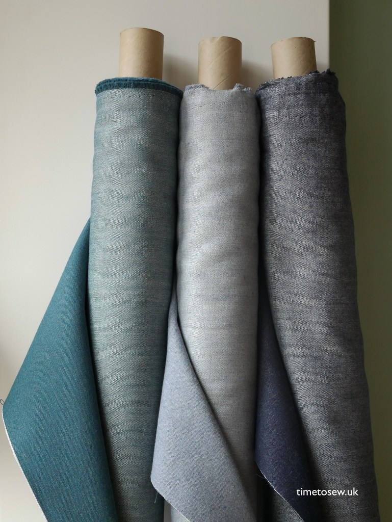 Three rolls of denim fabric in three different shades of blue