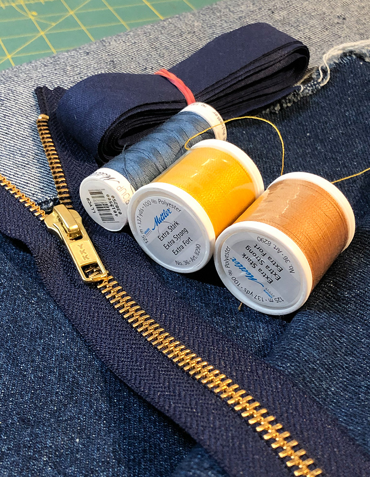 This picture shows three spools of thread. Two spools contain extra strong thread, one spool contains normal sewing thread. There is some folded dark blue bias tape stick together with a rubber band. And it shows a dark blue zipper with golden teeth. Everything is located on some dark blue denim fabric.