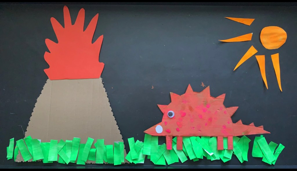 A child's artwork made of cut-out coloured paper. On the left, a volcano erupts;  on the right, a spiky dinosaur with a googly eye looks on, under a bright sun. There is grass made of strips of green paper.