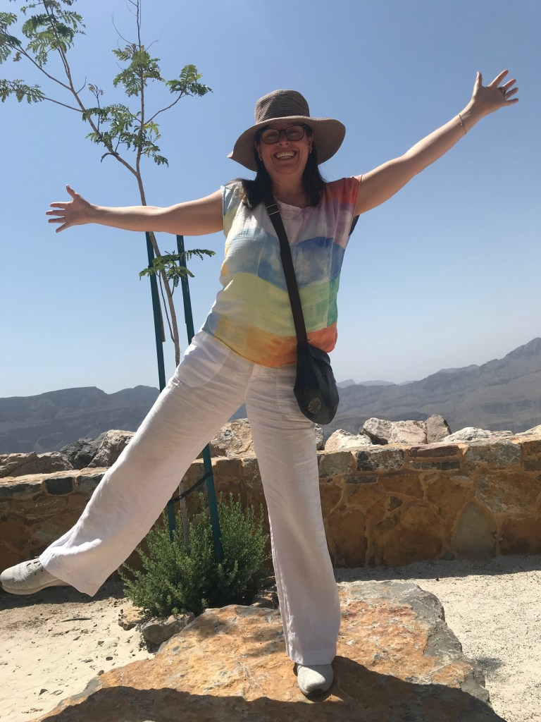 A picture of the author Joanne, wearing a colourful top she made, white linen pants and a hat.  She is posing at the top of a mountain.