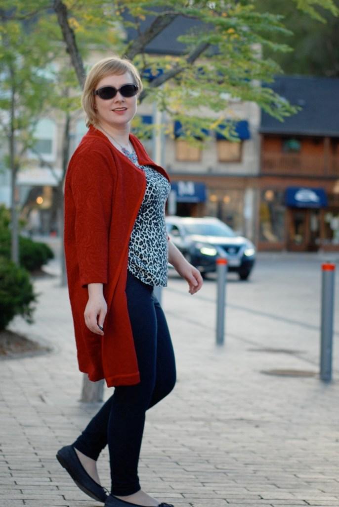 Gillian wears a rust orange coatigan, a leopard print tank/cami, and dark leggings, all made herself.