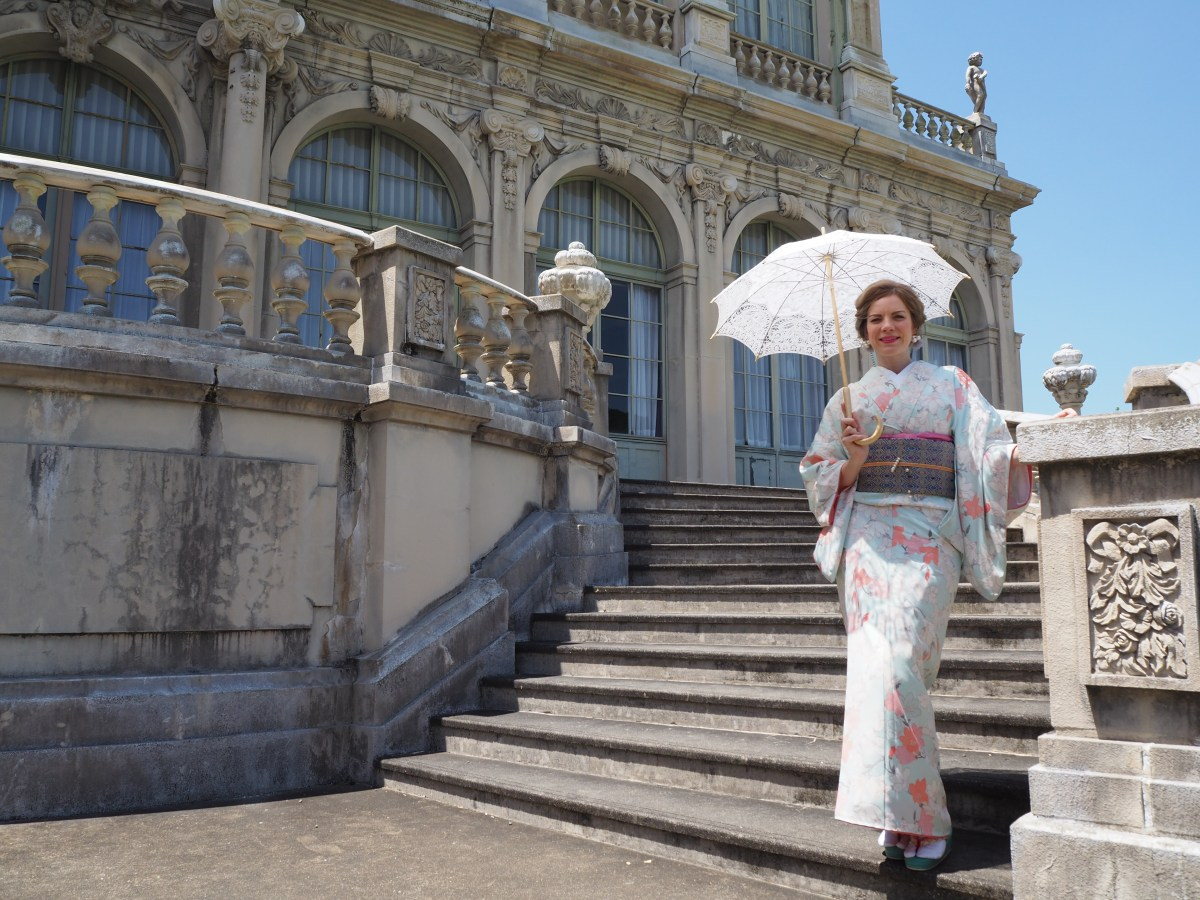 Billy stands in front of a Baroque building, wearing a light colored kimono with flowers, and covering herself with a parasol.