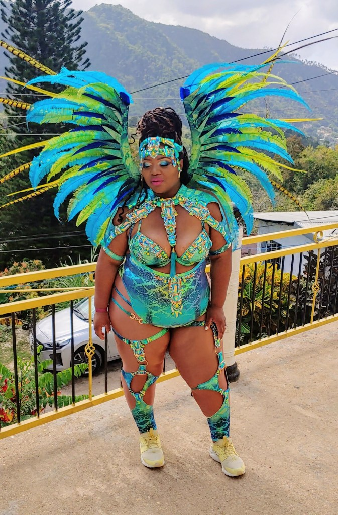 Martha wears an elaborate Carinval costume, with strappy bikini and cutaway leggings, a glittery harness, and bright blue and yellow wings. She has a matching spangled headband as well.