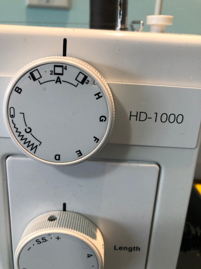 Kerry's sewing machine dial showing the three parts of its button-hole settings: left bar, right bar, and top/bottom bar.