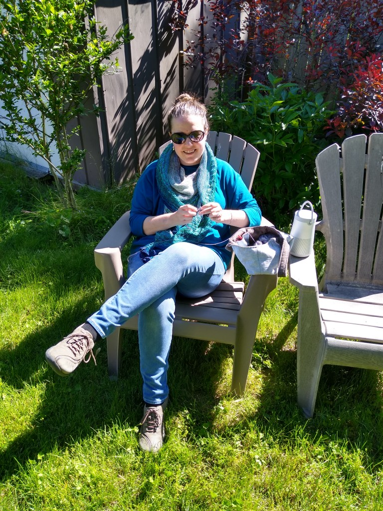 Anne, a white woman in her very late thirties, sits in a lawnchair in her back yard. She is wearing jeans and a teal Tessuti Isla top, with a hand knit shawl around her neck and more knitting in her hands.