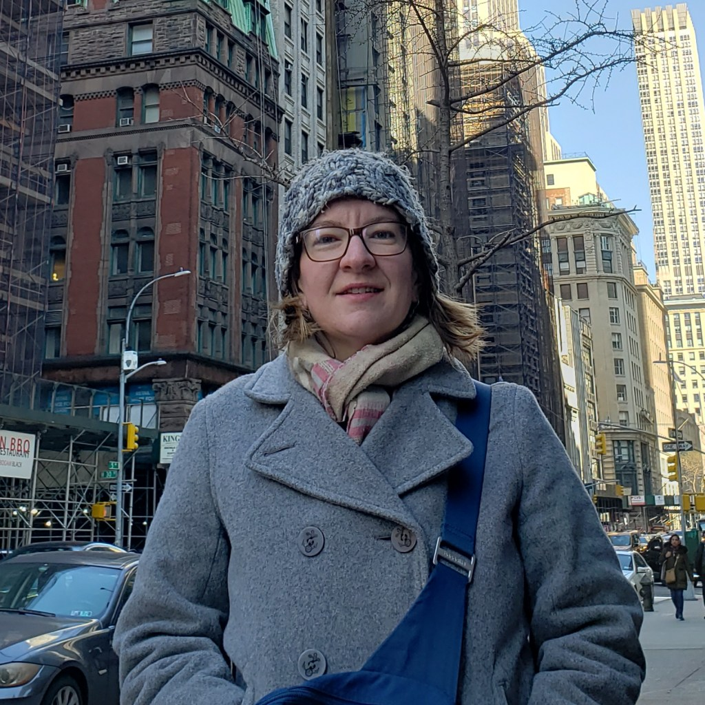 Kathryn, a white woman bundled up in a gray coat standing on a city street