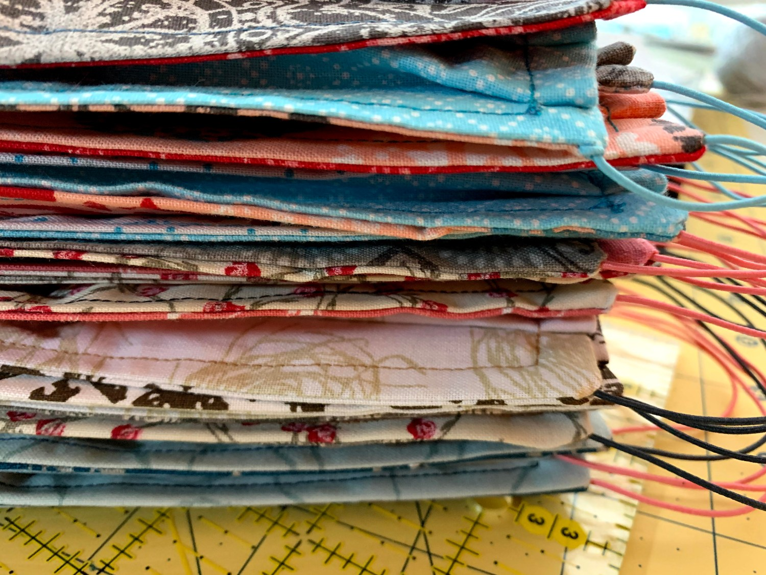 A stack of rectangular fabric masks that have color coordinated thin elastic ear loops. The masks are on top of a yellow cutting mat and a clear quilting ruler.