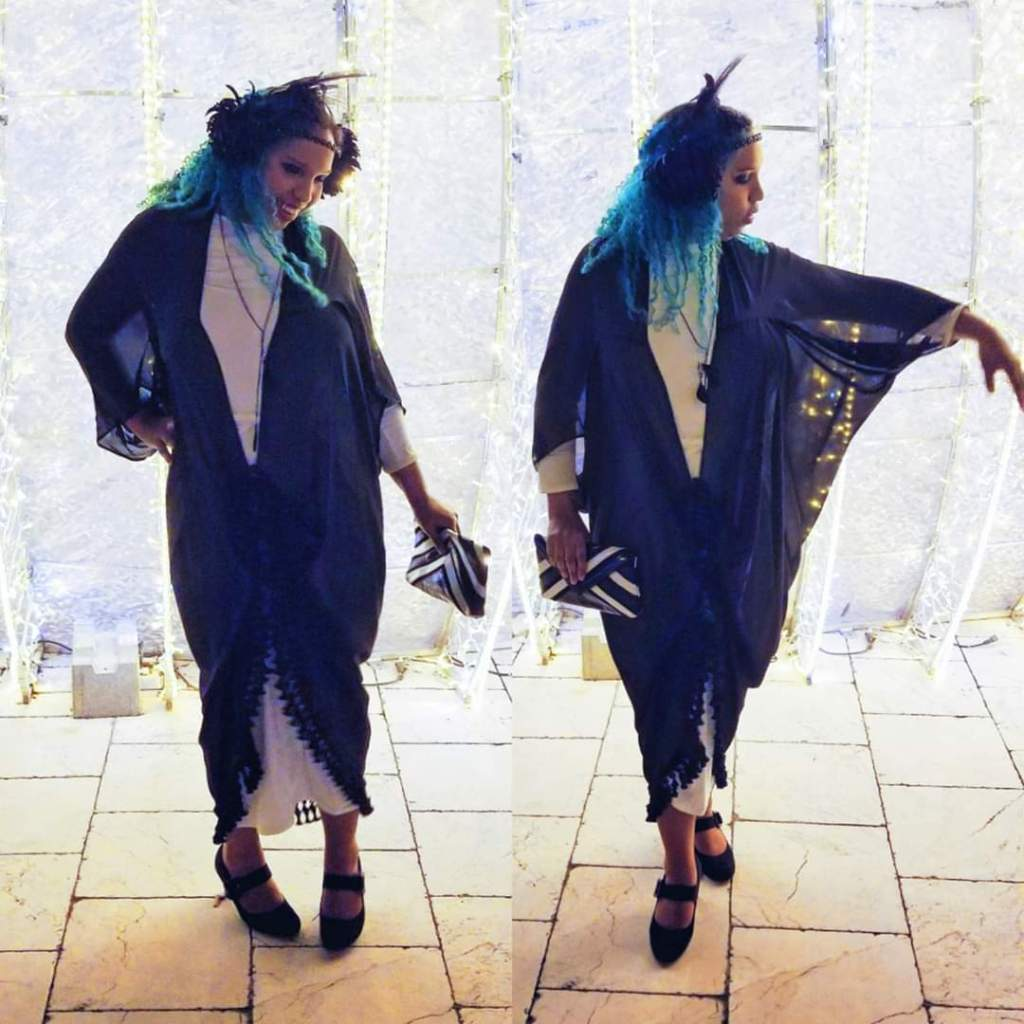 Whitney wears a 1920s silhouette with a sheer black batwing overdress/wrap, a white underdress, a feathered headpiece, neon blue hair, a striped clutch, and retro styled heels.
