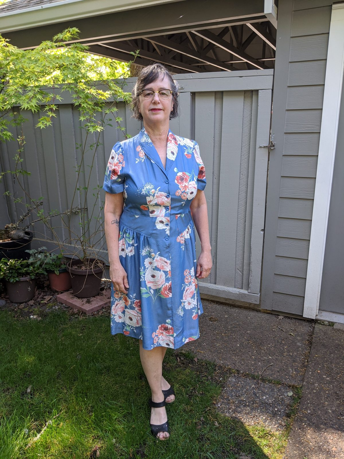 A white woman with short gray hair wears a light blue button front dress that has a pink floral design; it is knee length. She is standing outside in what appears to be the back or the side of a house.