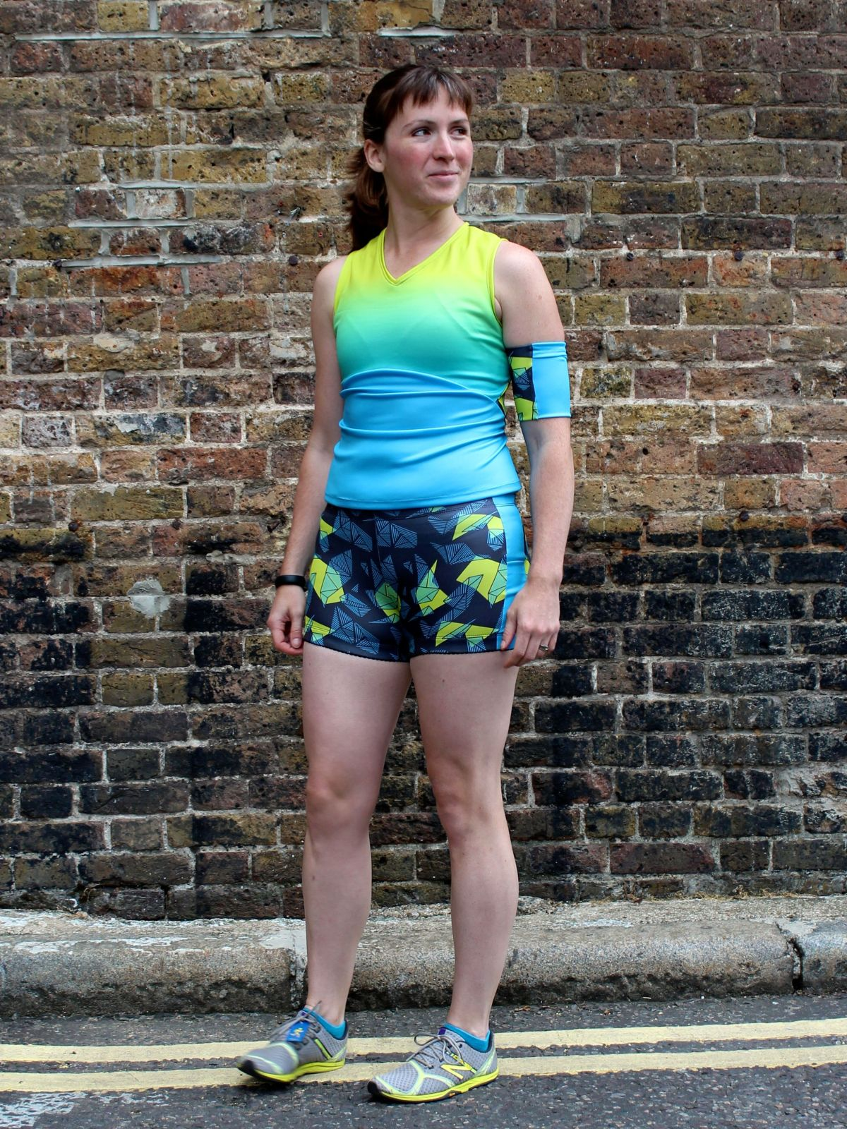 Melissa is standing in front of a brick wall and is wearing a sleeveless ombre activewear top, shorts with angular shapes on the fabric, and a matching device armband.