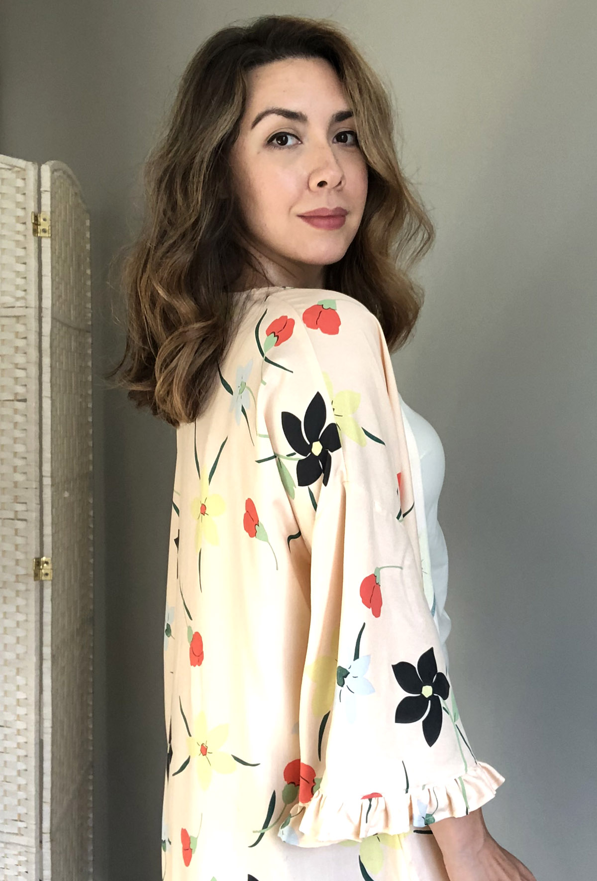 A woman with medium skin tone, brown eyes, and brown wavy hair looks over her right shoulder. She is wearing a light pink dress with a floral motif and the end of the sleeve has a short ruffle.