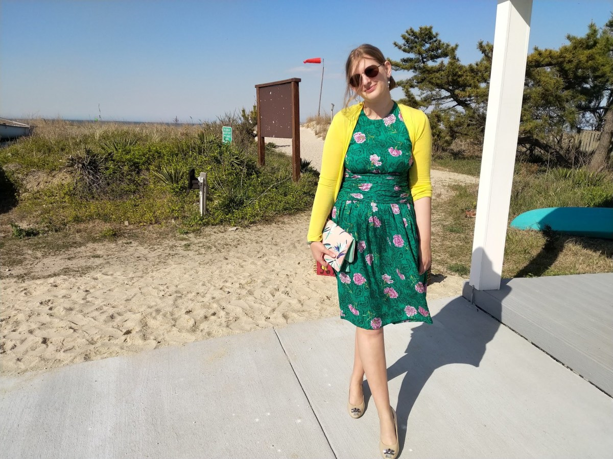 Allison is wearing sunglasses, a yellow cardigan, and a green dress with pink flowers on it. She is holding a clutch purse and she is standing at the entrance to a beach.
