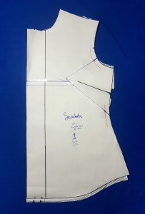 The pattern piece with blue marker lines on top of the original piece. The original pattern piece shows through slightly where the dart has been reduced and along the bottom.