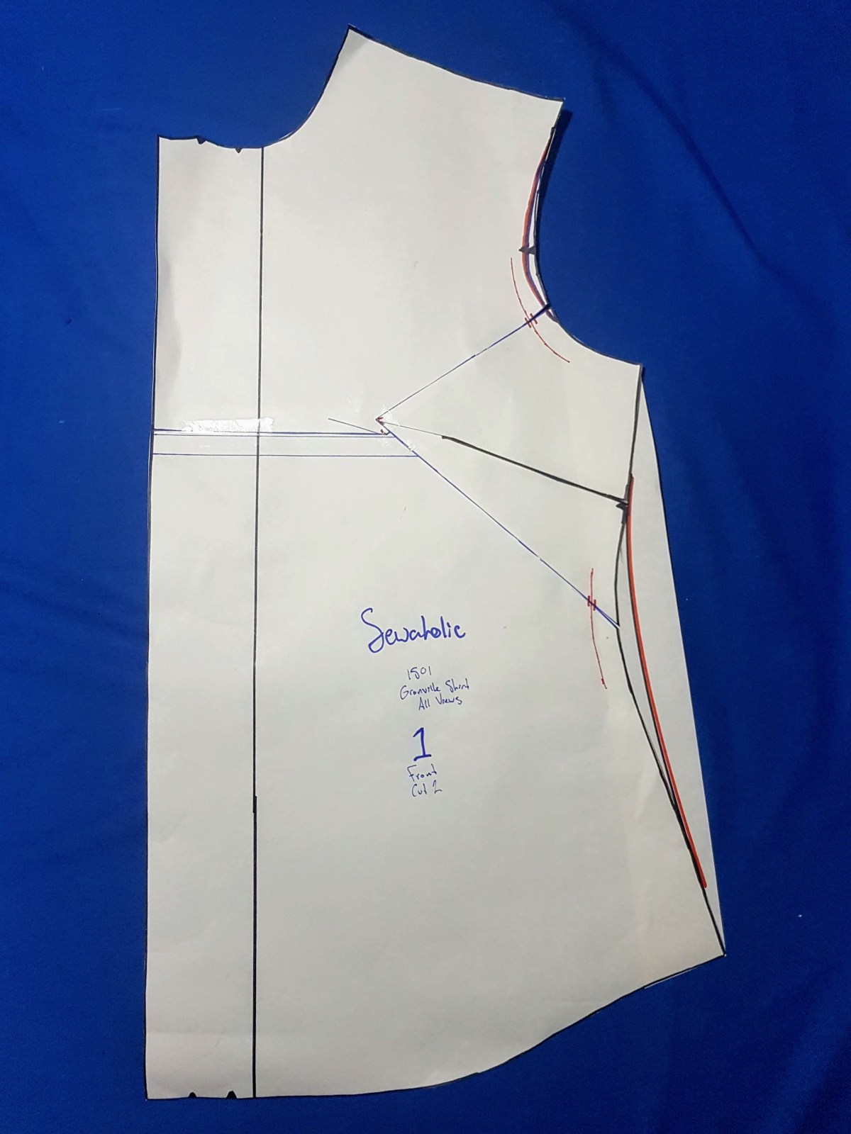 Pattern piece that has orange marker lines indicating an armsyce adjustment and lessening the curve of the waist to hip.