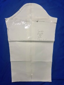 The sleeve pattern piece, with a full bicep adjustment and an excess of tape. The seam allowance is marked along the front.