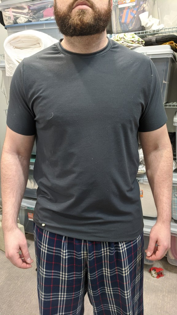 A photo of the author's husband from the front, wearing the first muslin of a dark-coloured tee shirt.