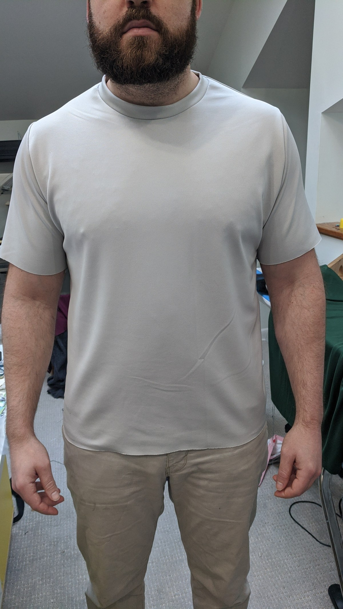 A photo of the author's husband wearing the final muslin, a plain tee shirt in a light grey colour.