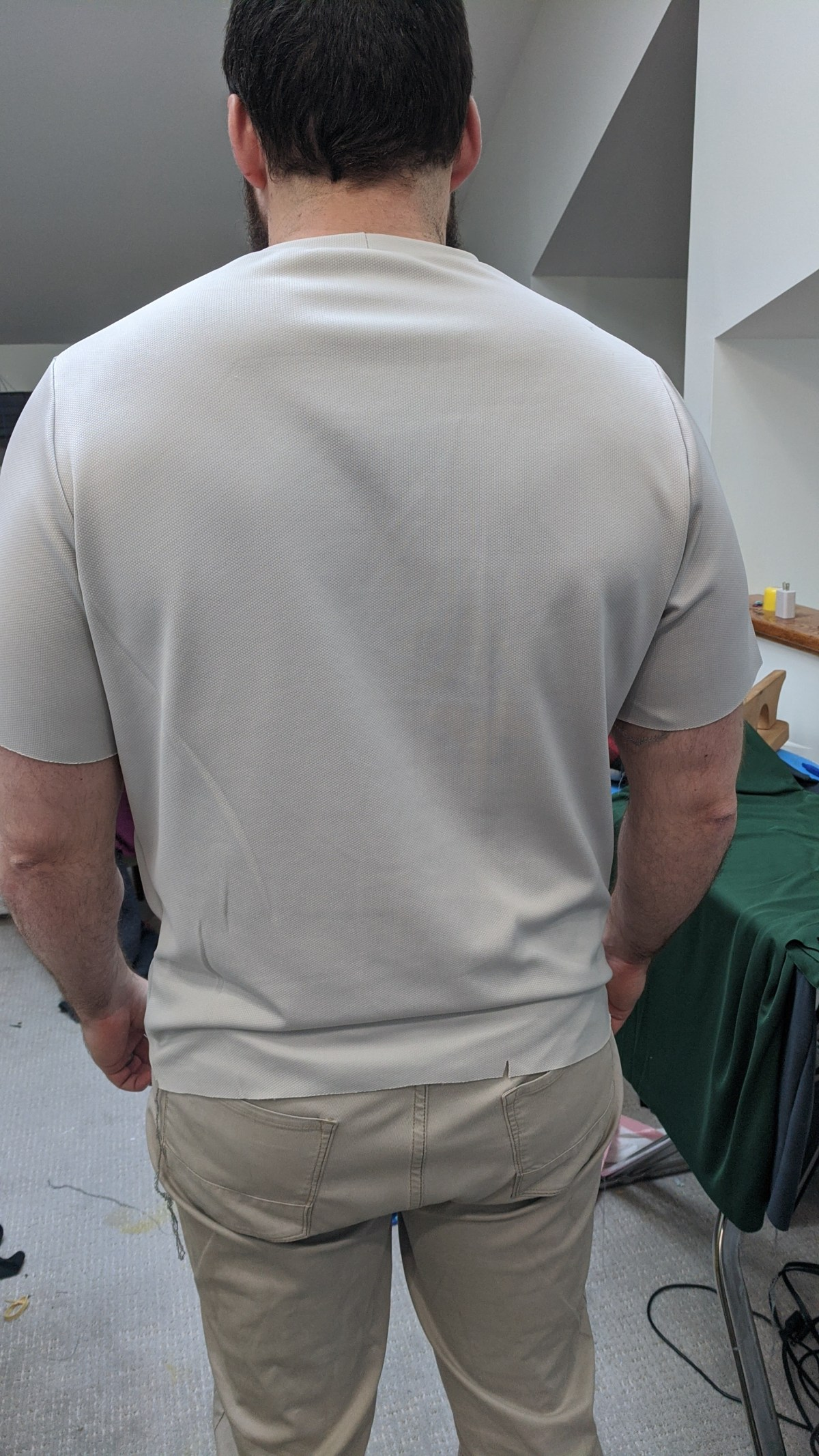 A photo of the author's husband wearing the third muslin, a light grey tee shirt, from the back.
