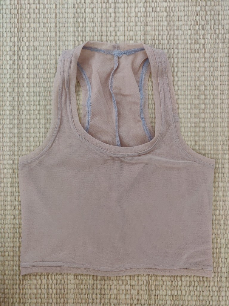 Another flat lay. This version of the tank is in a pinky-tan colour, and is made of power mesh. It has the same low neck cut as the last couple of versions.