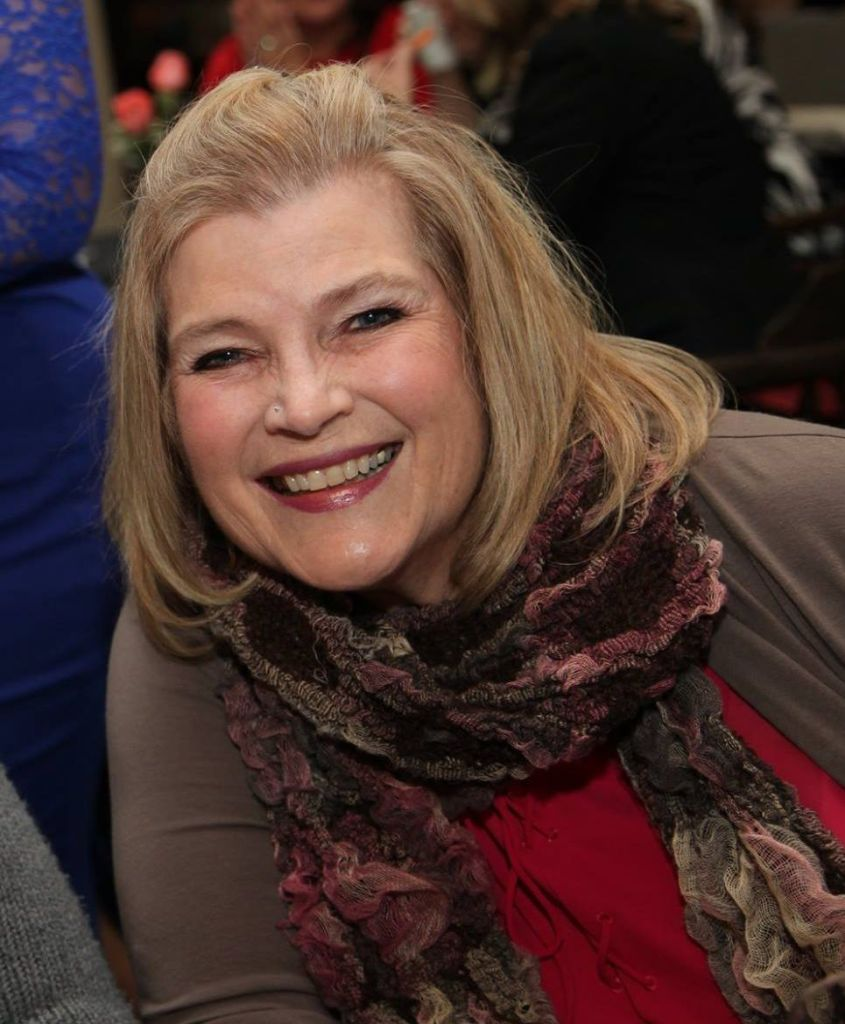Lynda, a blonde white woman, grins at the camera. She's wearing a textured scarf and is leaning into the picture.