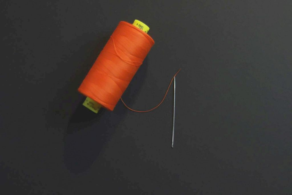 A hand sewing needle and a spool of bright orange thread