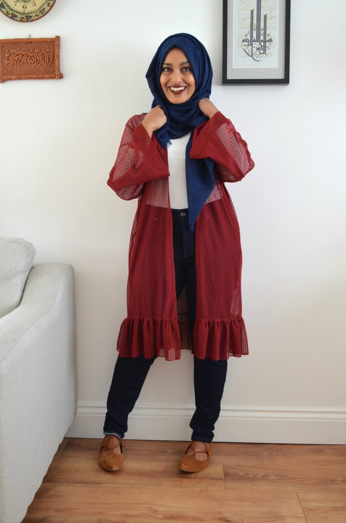 Photo of Rumana wearing a red sheer duster over dark trousers and a white top, paired with a blue hijab. Rumana is standing in her home, and is looking towards the camera.