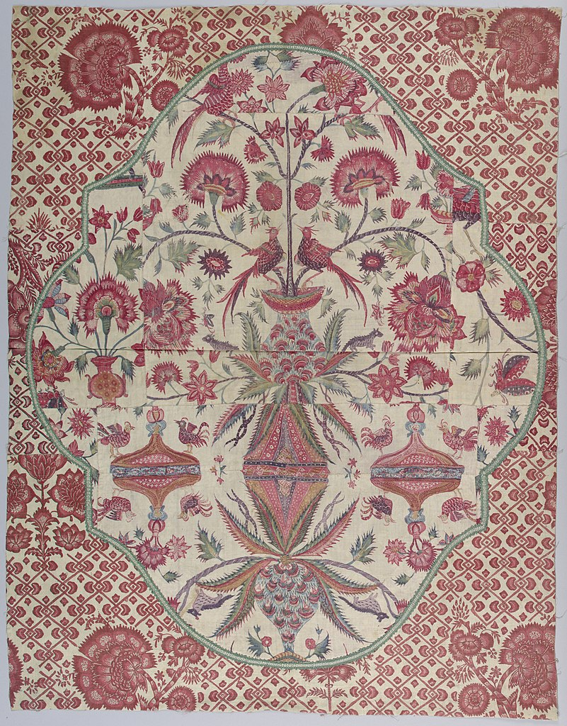 Textile with an intricate pattern, predominately in red