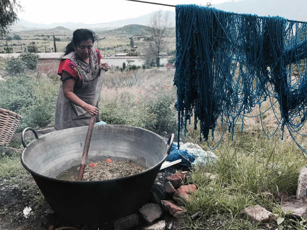 A woman is outdoors, stirring water and dyestuffs in a very large metal pot, using a long pole. Yarn dyed blue hangs on a washing line.