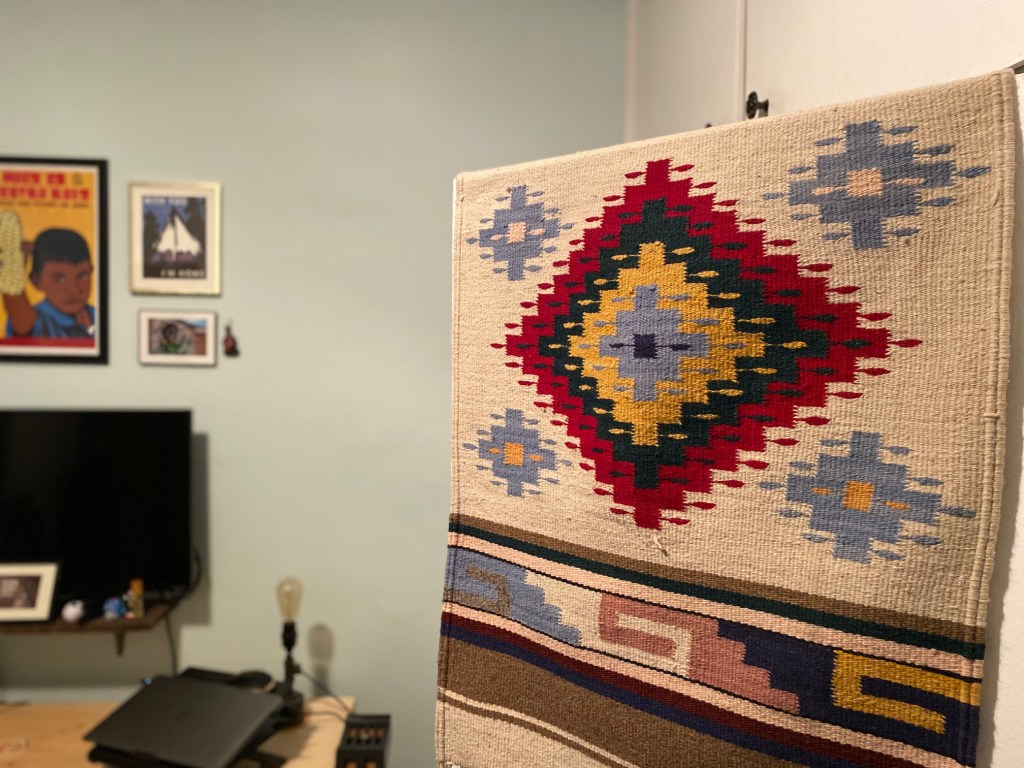 A woven rug hangs in Cynthia's study, displaying typical diamond patterns in red, blues, yellow and ecru.
