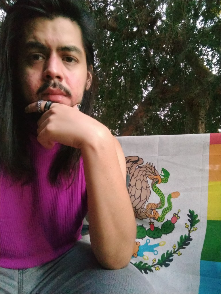 Person with long hair in front of a colored flag