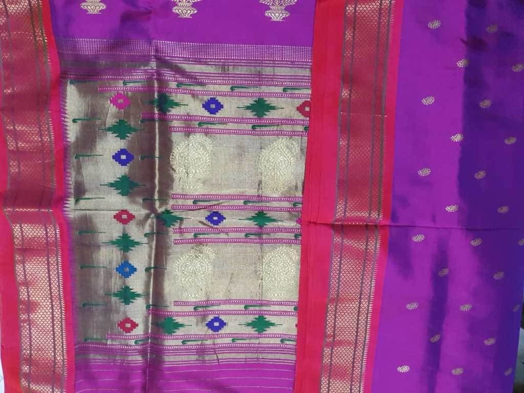 A purple Paithani showing a red and gold border and the featured silver pallau panel with it's geometric motifs in purple, pink and green.
