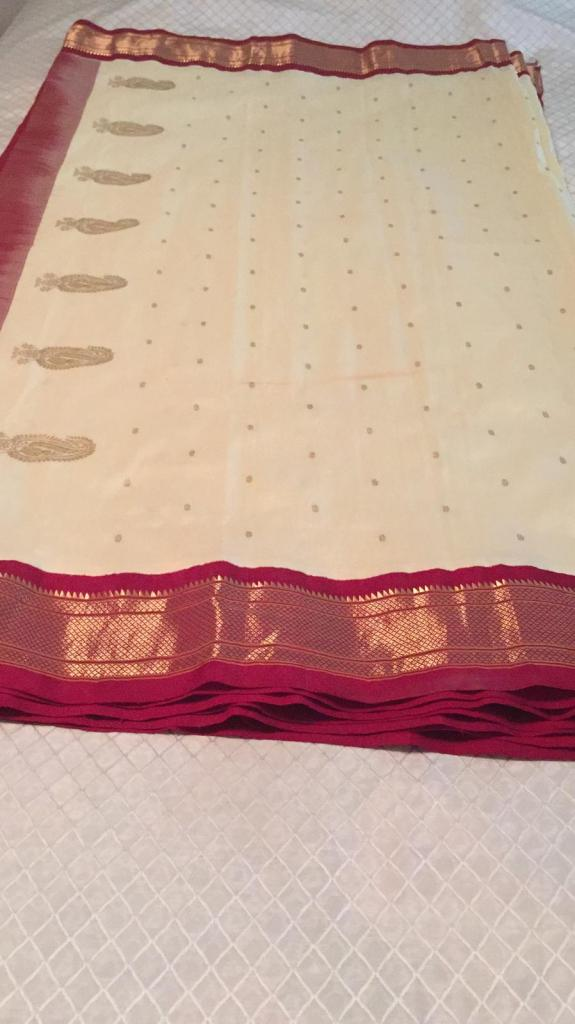 A folded Paithani lies on a bed. The main colour is off-white, and it has a gold and pink border around all edges, with gold paisley and small gold dots woven all over into the main part of the cloth.