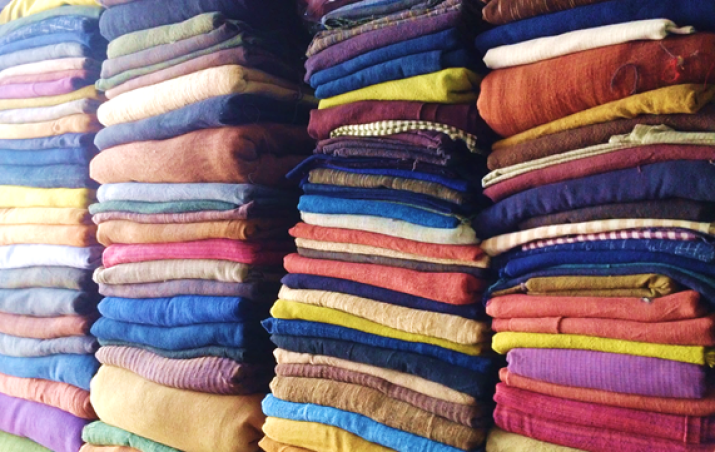 Image of piles of multicoloured cotton fabric neatly folded and stacked on top of each other