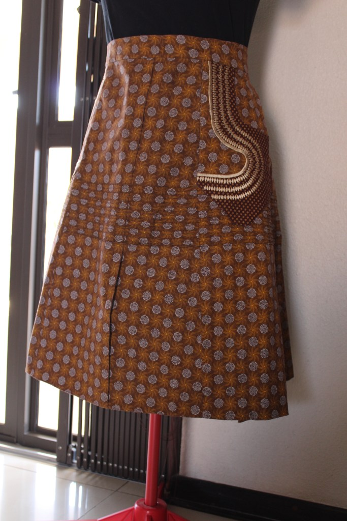A patterned skirt on a dressmaker's dummy. The skirt has white and gold floral motifs on a brown background, There is a feature pocket with browm dotte fabric and gold embroidered highlights.