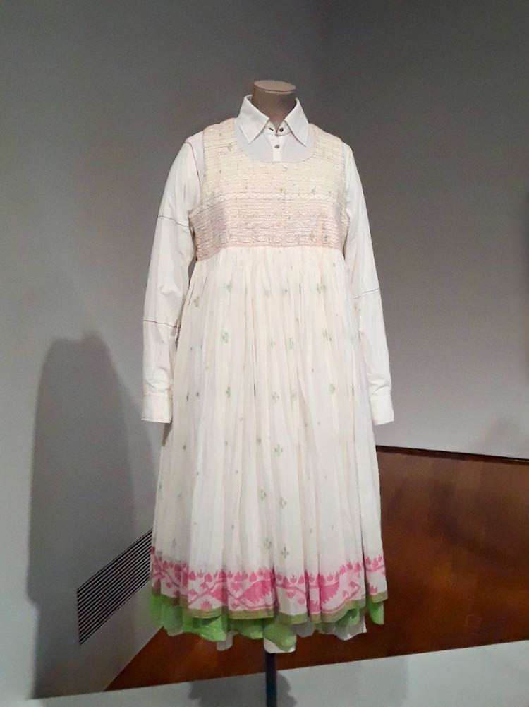 Dress made of white jamdani fabric with woven green dots all over and bright pink woven border design at hem. Designed by Aneeth Arora for clothing brand Pero.