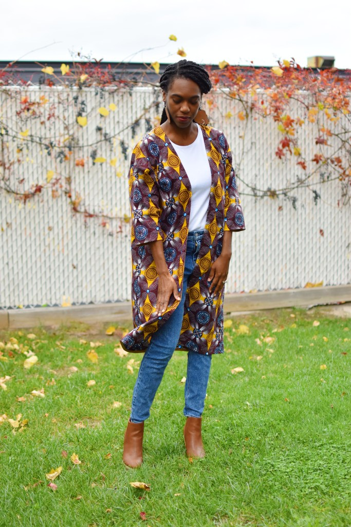 Person in jeans, a T-shirt and a long jacket made of an Ankara print with yellow, burgundy and other colors