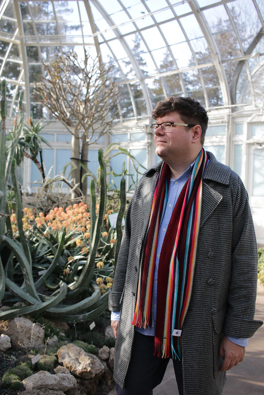 Phil (a white man in his 30s) is stood in a large greenhouse wearing a long black and white coat paired with a stripey scarf.