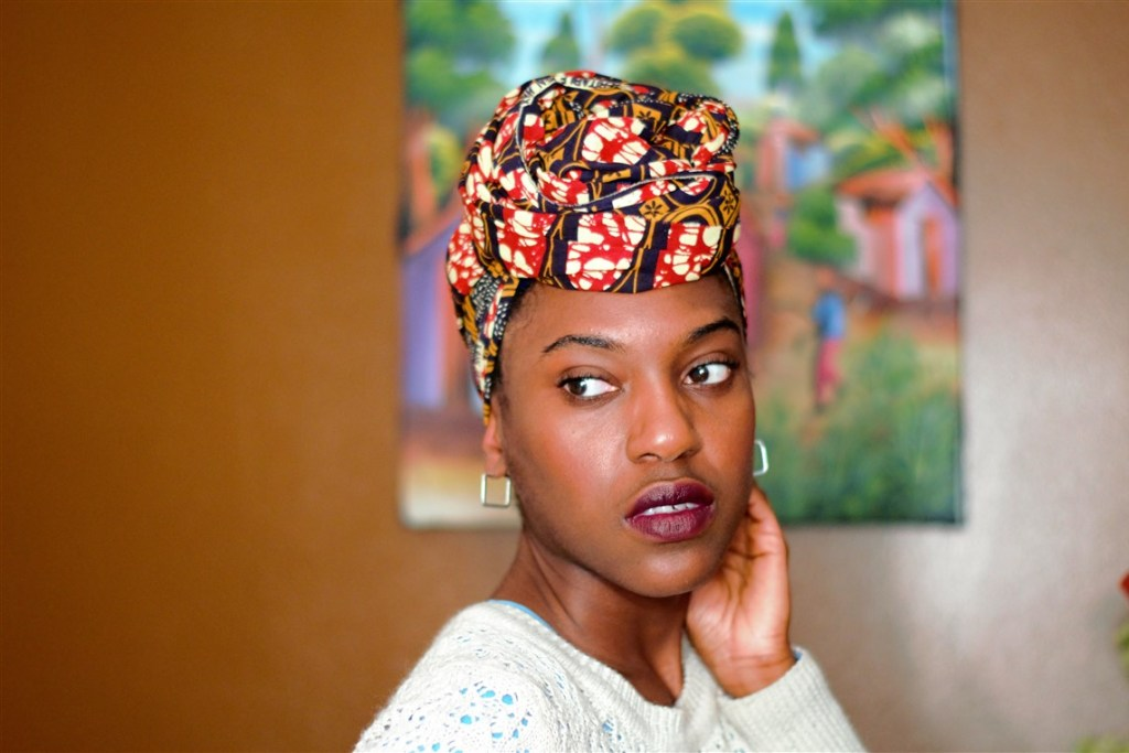 Headshot of a person with a headwrap made of Ankara fabric with red, yellow and other colors