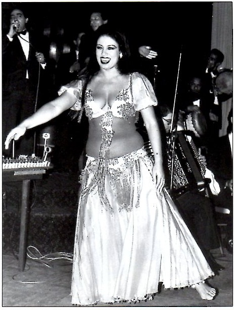 Black and white photo of a woman in a crop top and long flowy pants